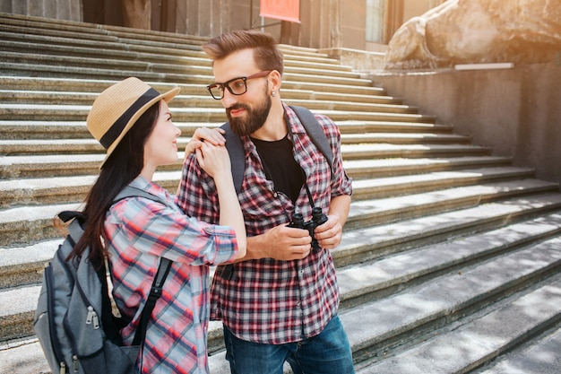 Attractive young man and woman stand on stairs and look at each other. she holds hands on his shoulders. they smile to each other. people look lovely.