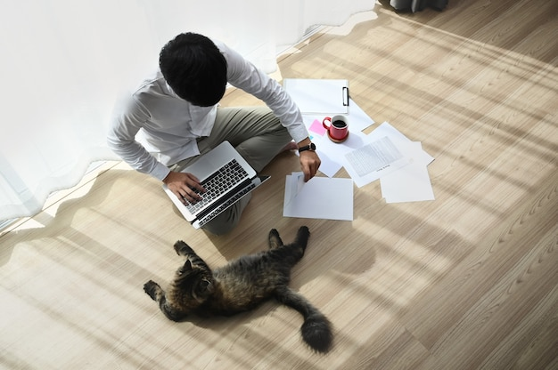 Attractive young man working on a laptop while sitting with a cat on floor in a comfortable home .