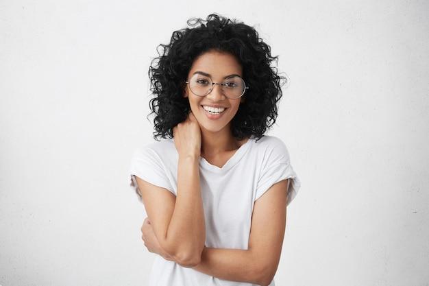 Attraente giovane donna di razza mista con un sorriso affascinante che indossa occhiali alla moda