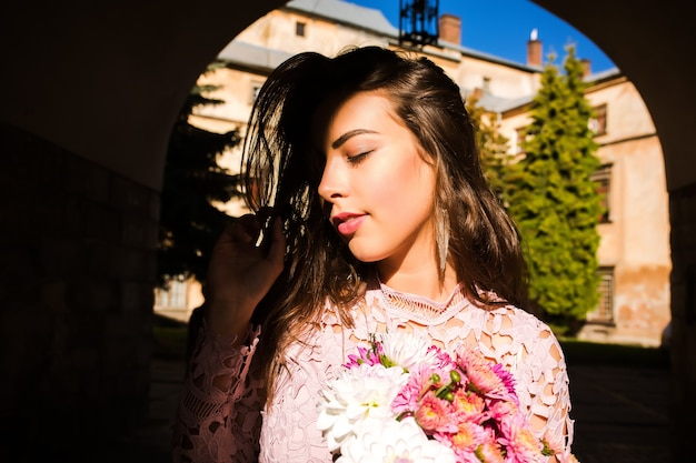 花の花束を保持している魅力的な若いモデル。彼女の顔に影を付けて通りでポーズをとる女性