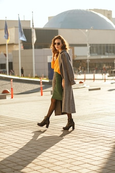 Attractive young model with curly hair in sunglasses wearing trendy outfit and walking down the sunny street