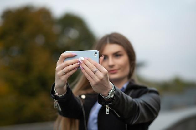 公園で携帯電話で自画像を作る長い髪の魅力的な若いモデル