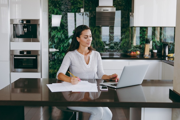 The attractive young modern business woman working with documents and laptop in the kitchen at home