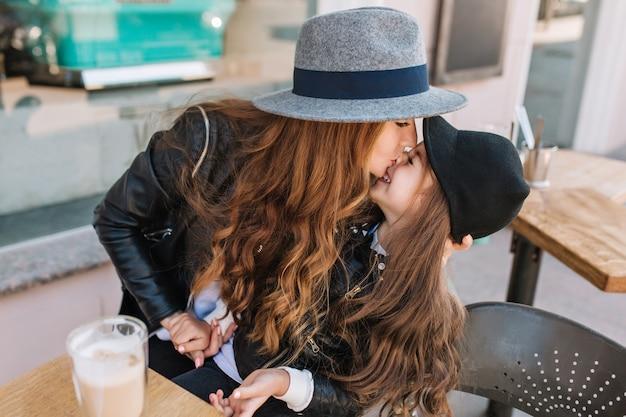 Attraente giovane mamma che indossa il cappello con nastro nero divertente che bacia la figlia nel naso, mentre lei ride.