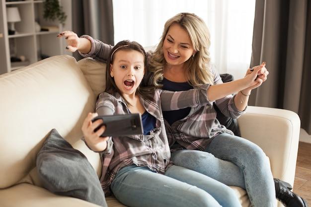 魅力的な若い母親と幼い娘がスマートフォンを使って夫のために自分撮りをしています。