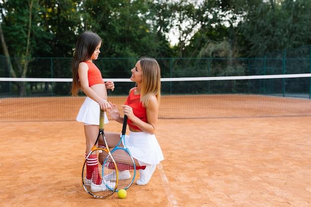 Привлекательная молодая мать помогает дочери играть в теннис