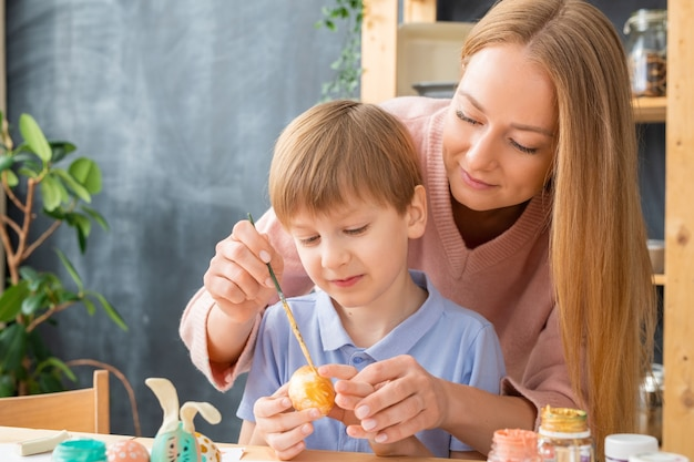 Attractive young mother using paintbrush while helping son to paint egg for easter decorations