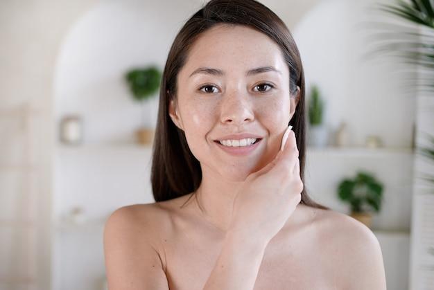 Привлекательная молодая многоэтническая женщина после ванны, очищающей кожу и поры с ватным диском, счастливая азиатская девушка, удаляющая макияж и грязь, наслаждается эффективной косметикой косметики по уходу за телом.