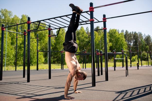 Привлекательный молодой мускулистый спортсмен делает стойку на руках на спортивной площадке в солнечный день с удобствами
