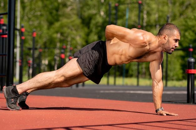 Привлекательный молодой мускулистый мужчина держит правую руку на спине, отжимаясь левой во время тренировки на открытом воздухе