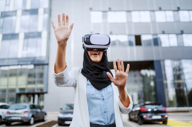 Attractive young muslim businesswoman with scarf on head using vr goggles for virtual presentation. millennial generation.