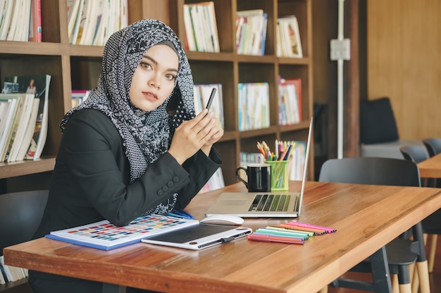 Attractive young muslim creative designer woman using pen tablets and laptop in front of bookshelf.