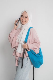白い孤立した背景の上に携帯電話を使用して魅力的な若いイスラム教徒の学生