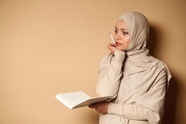 カメラの横にヒジャーブを着た魅力的な若いイスラム教徒の女性。片方の手に開いた日記、もう片方の手に鉛筆をあごの近くに置き、しんみりと横を向いています。