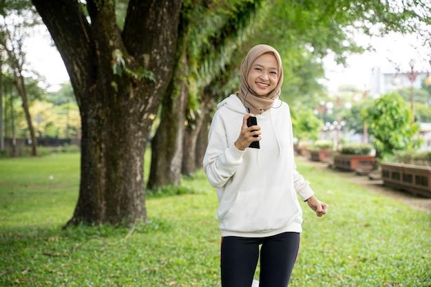 Привлекательная молодая мусульманская женщина работает открытый. улыбающаяся счастливая азиатская спортивная девушка бегает трусцой