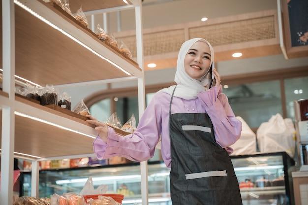 彼女の店にいる間に電話をかける魅力的な若いイスラム教徒の女性。忙しいビジネスワーカー