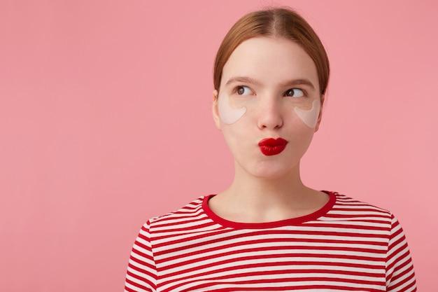 Привлекательная молодая таинственная рыжеволосая женщина с красными губами и пятнами под глазами, одетая в красную полосатую футболку, смотрит в левую сторону, что-то замышляет, стоит на розовом фоне.