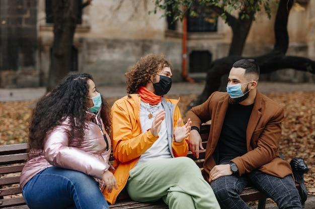 ベンチでリラックスしておしゃべりする保護フェイスマスクの魅力的な若者。秋の公園で余暇を過ごす幸せな多文化の人々。