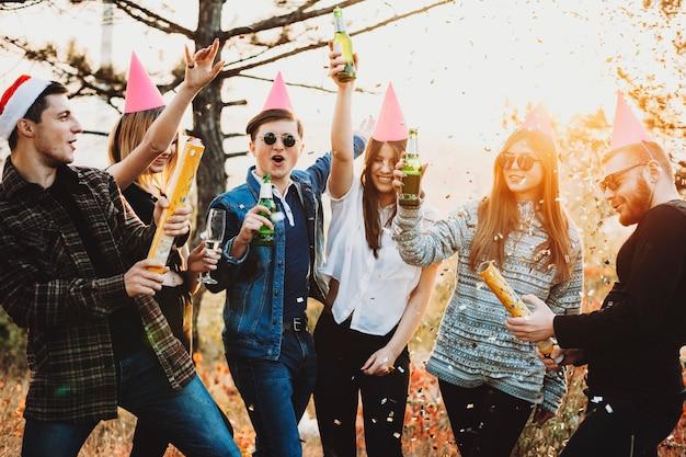 시골에서 크리스마스 축하 기간 동안 맥주 잔을 높이고 색종이 크래커를 폭발시키는 매력적인 젊은 사람들