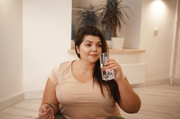 Привлекательная молодая женщина большого размера с пухлыми щеками и пышными формами сидит на полу дома в спортивной одежде, держит стакан, пьет чистую пресную воду, освежается после тренировки