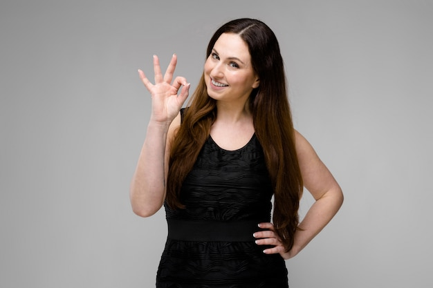 Attractive young positive brunette caucasian smiling woman in black dress showing ok sign isolated on gray