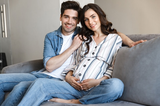 Attractive young pregnant couple relaxing on a couch at home, hugging