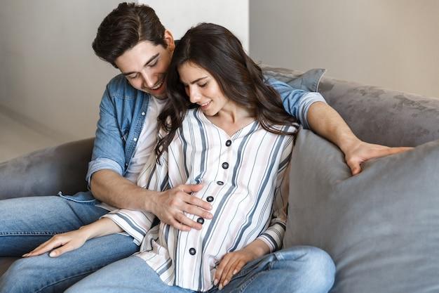 Привлекательная молодая беременная пара отдыхает на диване у себя дома, обнимая