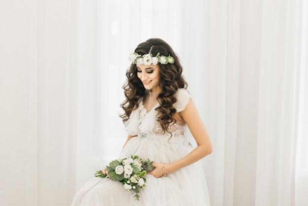 Привлекательная молодая беременная девушка в белом платье с завитками, венок и букет цветов. фотосессия в ожидании малыша