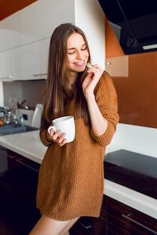 Привлекательная молодая красивая женщина с белой чашкой чая, глядя из камеры на современной кухне в солнечное осеннее время утра.