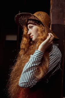 彼女の顔に影のある麦わら帽子の魅力的な若い赤い髪のモデル