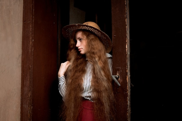 Attractive young red haired model with long wavy hair in straw hat posing near old door