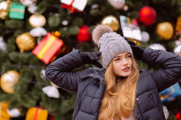 クリスマスのトウヒの背景にポーズをとって、冬の服を着て魅力的な若い赤い髪の女性