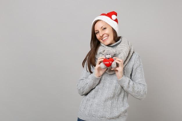 灰色のセーター、灰色の背景で隔離のテディベアぬいぐるみを保持しているスカーフクリスマス帽子の魅力的な若いサンタの女の子。明けましておめでとうございます2019お祝いホリデーパーティーのコンセプト。コピースペースをモックアップします。