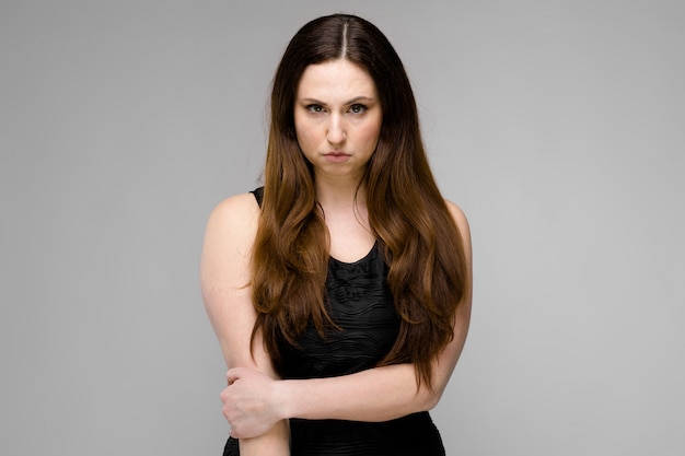 Attractive young serious angry brunette caucasian business woman in black dress isolated on gray