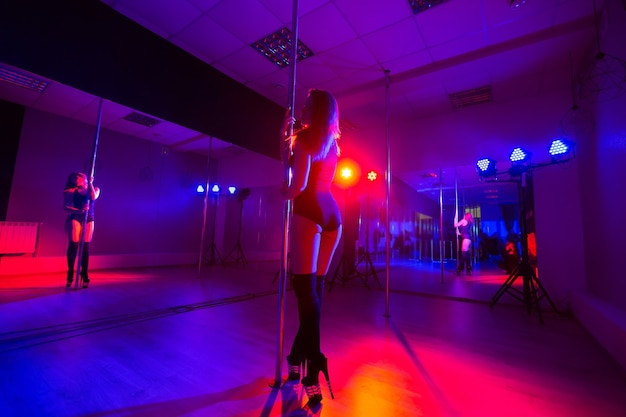 Attractive young sexy female pole dancer performs