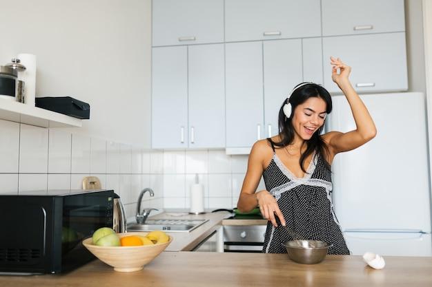 Привлекательная молодая тощая улыбающаяся женщина с удовольствием готовит яйца на кухне утром за завтраком, одетая в пижамную одежду, слушает музыку в наушниках, танцует