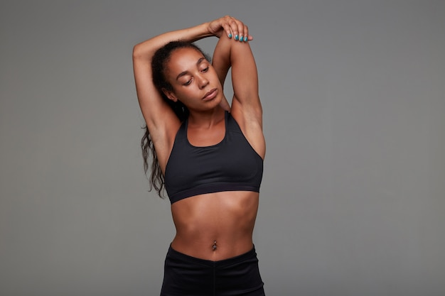 Attractive young slim dark skinned curly brunette female stretching her muscles before workout, goes in for sport every morning before her work, isolated