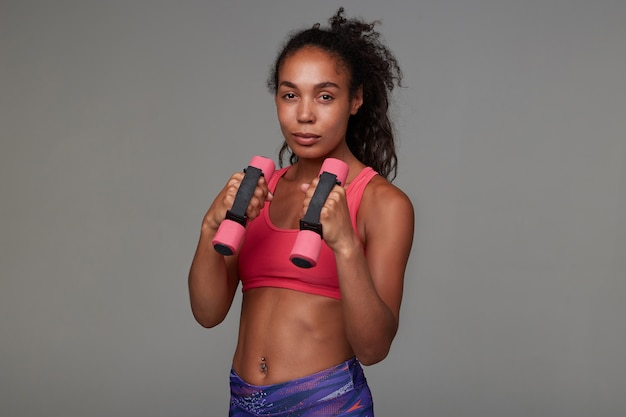 Attractive young slim dark skinned curly woman lady with ponytail hairstyle holding weighting agents in raised hands while exercising indoor, standing