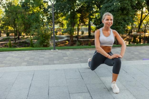 屋外でトレーニングする前にストレッチやウォームアップのエクササイズを行うスポーツウェアに身を包んだ魅力的な若いスリムなフィットネス女性