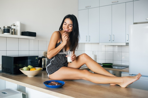 Attractive young slim smiling woman having fun at kitchen in morning having breakfast dressed in pajamas outfit eating cookies drinking milk, healthy lifestyle, long skinny legs