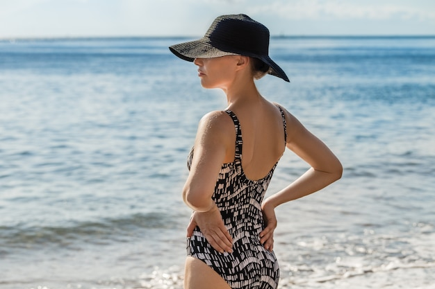 Attractive young slim woman in swimsuit and black hat