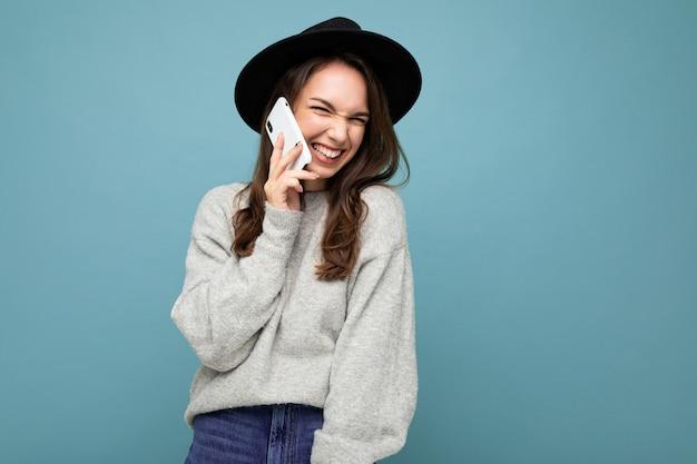 Привлекательная молодая улыбающаяся смеющаяся женщина в черной шляпе и сером свитере, держащая смартфон