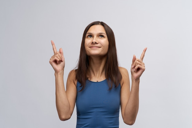 Attractive young smiling woman girl in tight blue t-shirt and with long straight dark hair looks up and forefinger pointed upward. the concept of ad space and the view direction