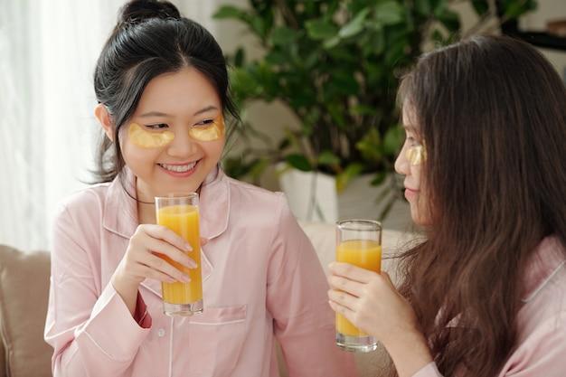 彼女の親友と家で時間を過ごすときにジュースのグラスを飲む目の下のパッチを持つ魅力的な若い笑顔の女性