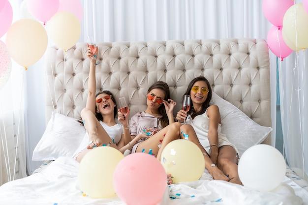 침실에서 파자마 파티를하는 동안 샴페인을 마시는 잠옷에 매력적인 젊은 웃는 여성