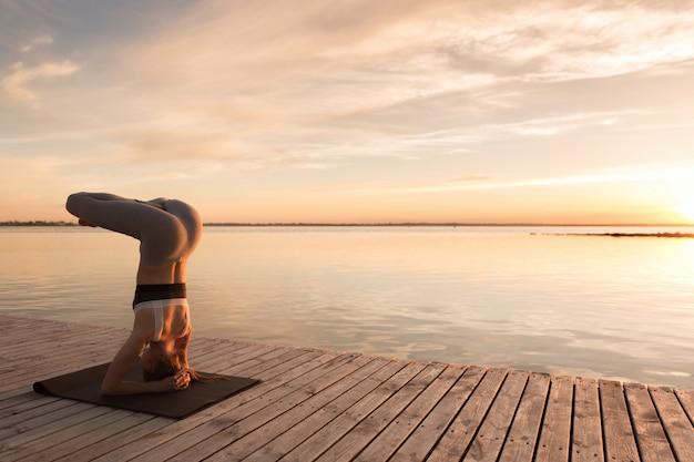 Привлекательная молодая спортивная леди делает упражнения йоги.