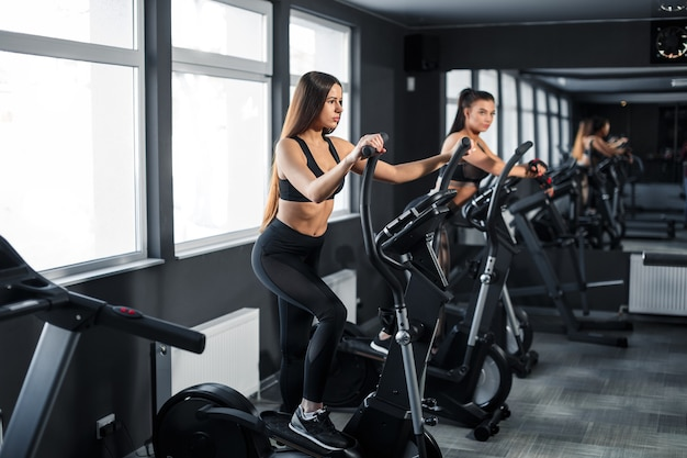 Attractive young sports woman is working out in gym. doing cardio training on treadmill. running on treadmill. high quality photo