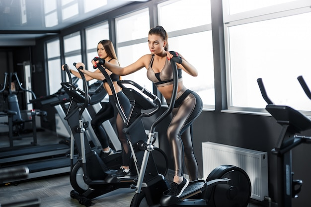 Attractive young sports woman is working out in gym. doing cardio training on treadmill. running on treadmill