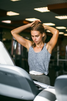 Attractive young sports woman is working out in gym.