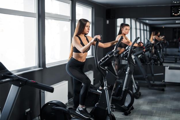 매력적인 젊은 스포츠 여성이 체육관에서 운동하고 있습니다. 트레드밀에서 유산소 운동을 하고 있습니다. 러닝 머신에서 실행. 고품질 사진